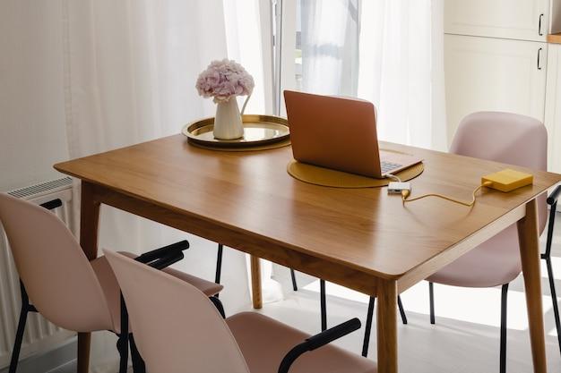 ノートパソコンと明るい晴れた日にキッチンの木製のダイニングテーブルの上の花が付いている瓶