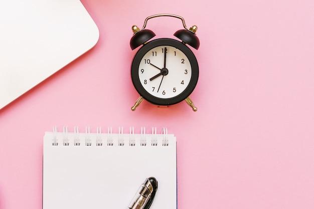 Ноутбук и белый блокнот с ручкой и черным будильником, стрелки указывают на восемь утра ...
