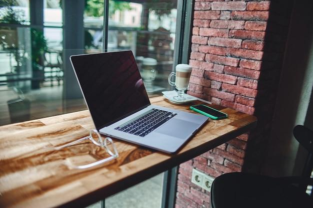 Ноутбук для удаленной интеллектуальной работы у окна в кофейне. уютное рабочее место