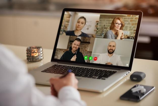 男の肩越しのオンライン会議中の電気通信アプリケーションのラップトップ画面ビュー。