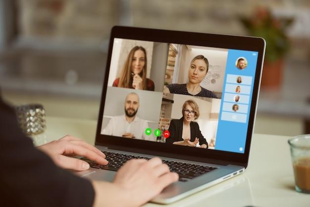 女性の肩越しのラップトップスクリーンビュー。実業家がオンラインブリーフィングで同僚と声明を話し合っています