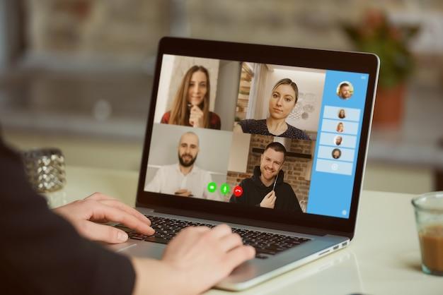 여자의 어깨 너머로 노트북 화면보기. 한 사업가가 동료들과 온라인 브리핑에서 성명을 논의하고 있습니다.