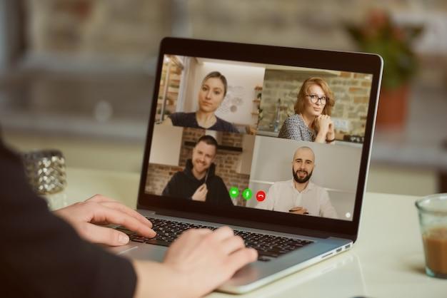 여자의 어깨 너머로 노트북 화면보기. 한 사업가가 온라인 브리핑에서 동료를 위해 성명서를 작성하고 있습니다.