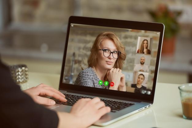 여자의 어깨 너머로 노트북 화면보기. 한 여성이 온라인 브리핑에서 동료들과 비즈니스를 논의하고 있습니다.