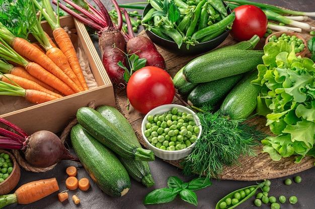 Большой ассортимент свежих овощей и зелени на коричневом фоне. вид сбоку.