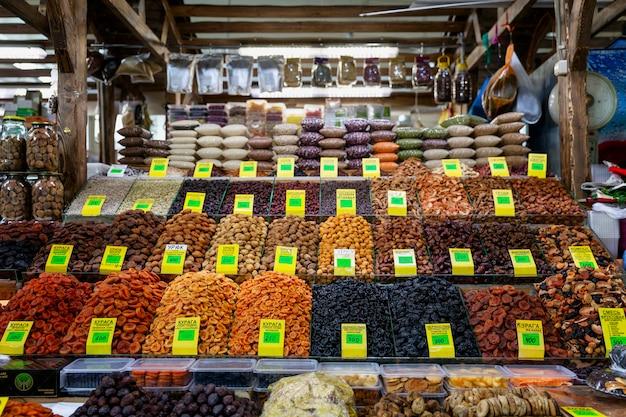 ナッツとドライフルーツの豊富な品揃えが市場のカウンターにあります。正面図。健康的な栄養と菜食主義。