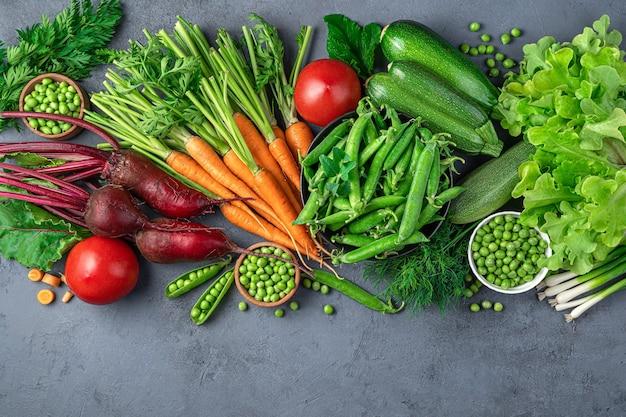 Большой ассортимент молодых овощей и зелени на синем фоне. вид сверху, копия пространства.