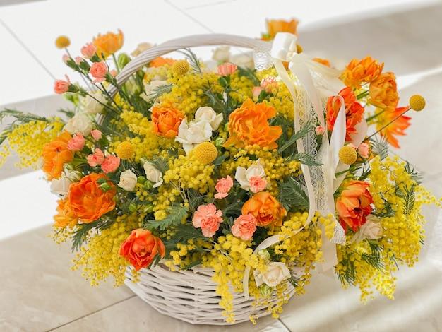 밝은 노란색 꽃이 있는 크고 아름다운 바구니. 오렌지 튤립과 봄 미모사. 휴가를 위한 낭만적인 선물. 꽃집의 배경 이미지