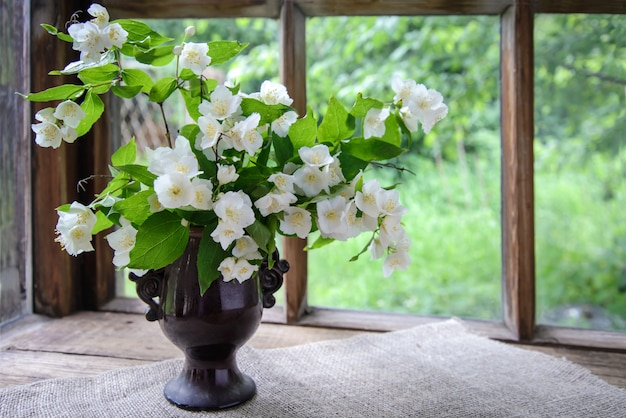 Большой красивый букет веток жасмина в вазе у деревянного окна на природе