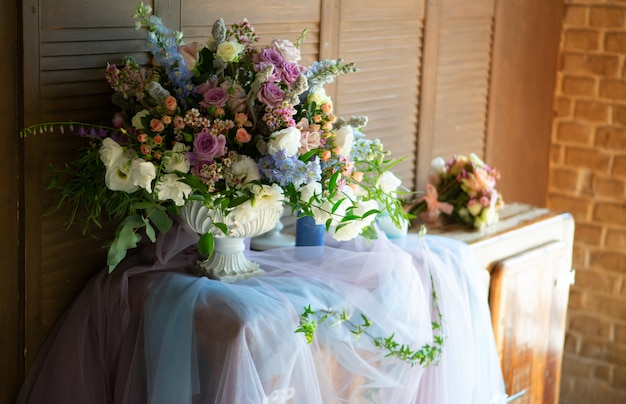 大きな美しい明るい花束は、明るい朝の日差しの中で古い箪笥に立っています