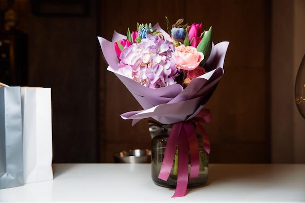 透明な花瓶に様々な種類の花の大きな花束が立っています
