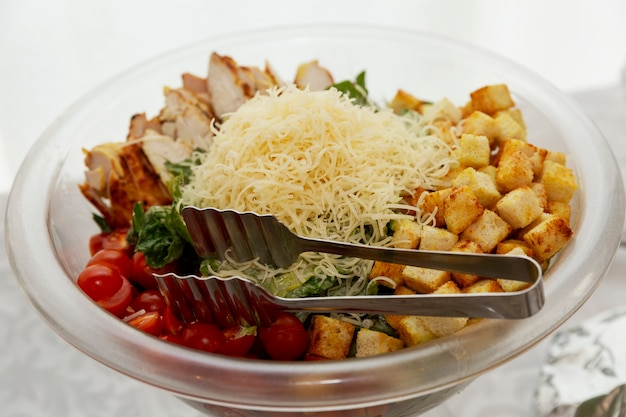 ビュッフェテーブルのサラダの大きなボウル。ビジネスミーティング、イベント、お祝いのケータリング。