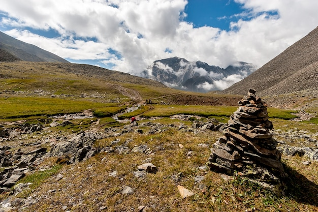 Большая пирамида из камней на переднем плане и большие горы на заднем плане. голубое небо с низкими белыми облаками над горами. по тропе идут несколько туристов с рюкзаками. по горизонтали.