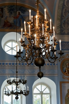 В церкви с потолка свисает большая люстра со свечами. фрагмент церковного интерьера