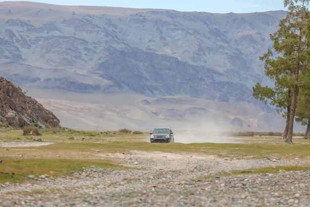 대초원을 가로 지르는 자동차 경주 뒤의 도로 먼지 구름. 백그라운드에서 산