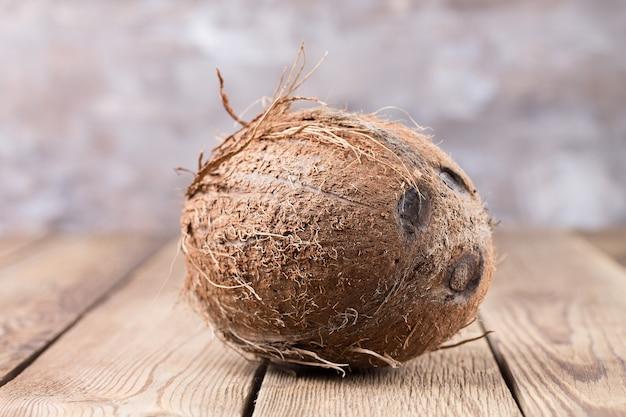 大きなココナッツは、明るくぼやけた背景の木製のテーブルの上にあります。健康食品。閉じる