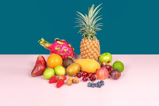 Большая коллекция различных фруктов на темно-зеленом и розовом фоне