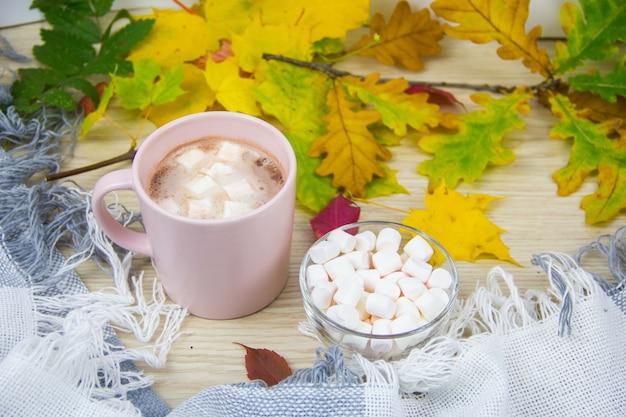 Большая чашка горячего какао с зефиром и теплое одеяло на фоне старого деревянного удава
