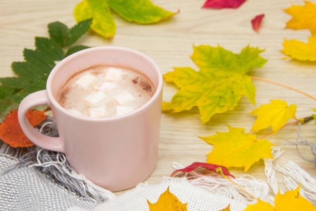 Большая чашка горячего какао с зефиром и теплое одеяло на фоне старого деревянного