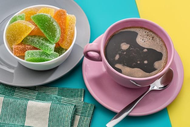 Большая чашка горячего пенистого кофе, разноцветный мармелад, салфетка и чайная ложка.