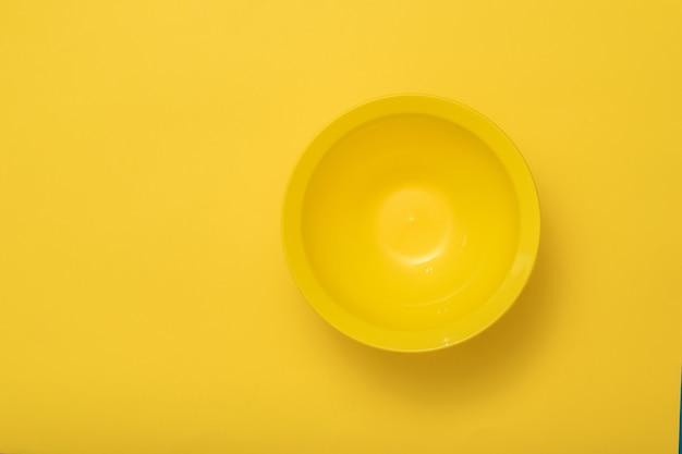 Большая темно-желтая миска на желтом фоне. пластиковая посуда для кухни.