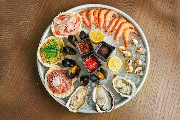 カキ、エビ、ムール貝、ホタテ-氷の上で新鮮なシーフードを使った大きな料理。閉じる。ケータリング