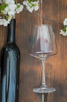 桜で飾られた木製のテーブルの上に大きな空のグラスとワインのオープンボトル。クラシックなワインと桜。