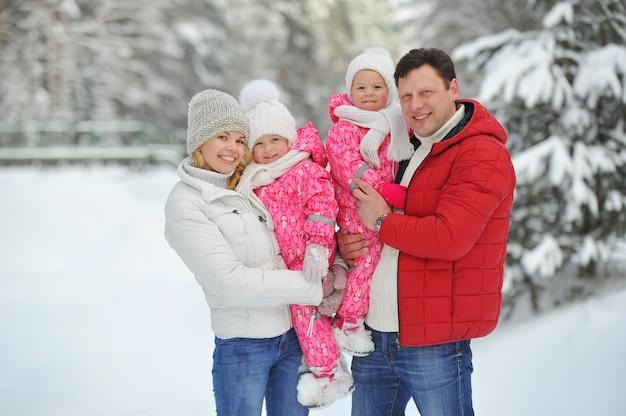 Большая семья с детьми на прогулке зимой в лесу.