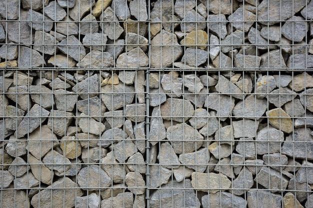 Большой забор из множества каменных валунов, поддерживаемый каменной решеткой по всей конструкции.