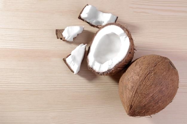 自然な木製の背景に大きな新鮮なココナッツとココナッツのかけら。上面図