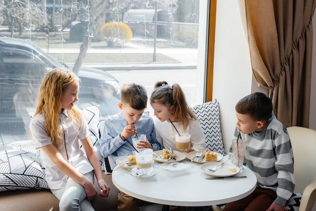 子供たちの大規模な友好的な会社が、おいしいデザートのあるカフェで休暇を祝います。誕生の日。