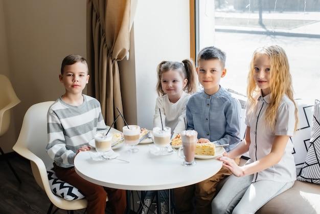 친근한 대기업 어린이들이 맛있는 디저트로 카페에서 휴가를 축하합니다. 출생일.