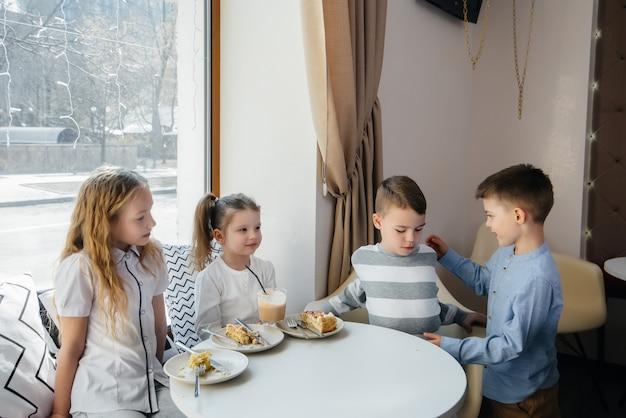 친절한 아이들이 맛있는 디저트로 카페에서 휴가를 축하합니다.
