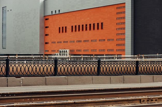 オレンジ色の壁のある大きな灰色の建物。カラフルな街。空の。