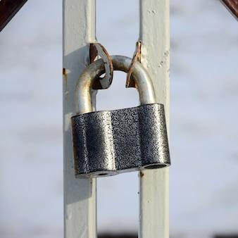 큰 회색 자물쇠가 금속 게이트에 달려 있습니다.