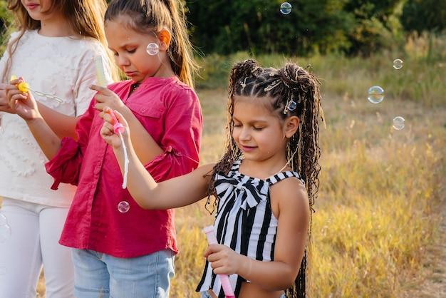 Большая компания веселых детей играет в парке и надувает мыльные пузыри. игры в детском лагере.