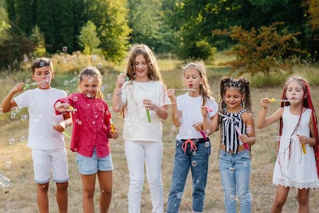 Большая компания веселых детей играет в парке и надувает мыльные пузыри