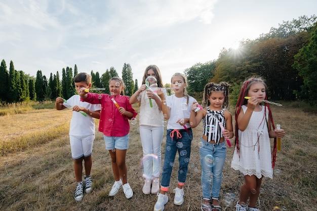 陽気な子供たちの大規模なグループが公園で遊んで、シャボン玉を膨らませます