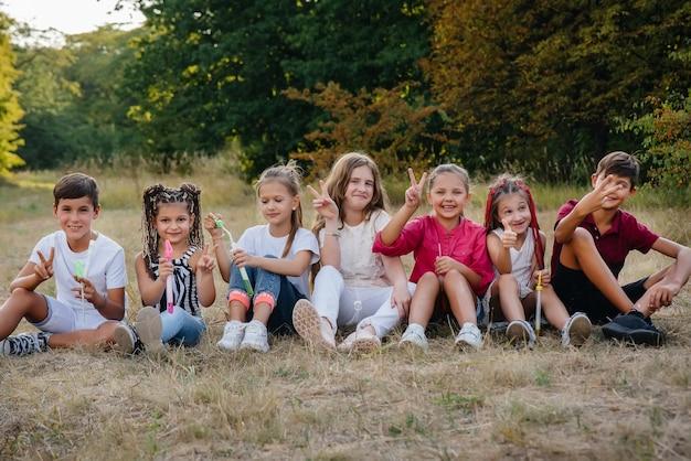 쾌활한 아이들의 큰 그룹이 공원의 풀밭에 앉아 미소를 짓습니다. 어린이 캠프의 게임.