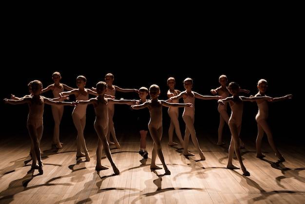 Большая группа детей репетирует и танцует балет.