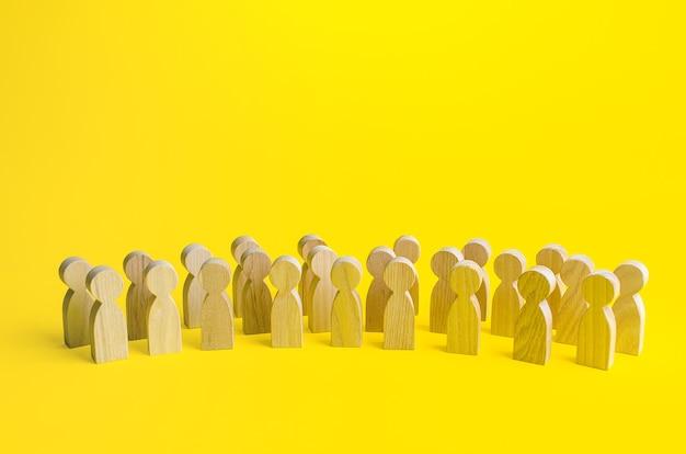 黄色の背景に人々の置物の大規模なグループ。社会調査と世論