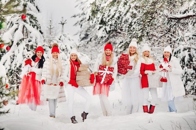 겨울 숲에 서 있는 손에 크리스마스 선물을 들고 있는 많은 소녀들. 눈 덮인 숲에서 크리스마스 선물을 들고 빨간색과 흰색 옷을 입은 소녀들