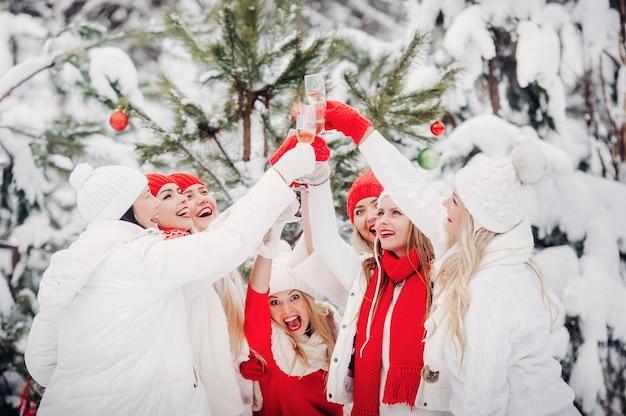 Большая группа девушек с бокалами шампанского в руках стоит в зимнем лесу. девушки в красно-белых одеждах с новогодними напитками в заснеженном лесу.