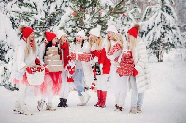 Большая группа девушек с бокалами шампанского в руках стоит в зимнем лесу