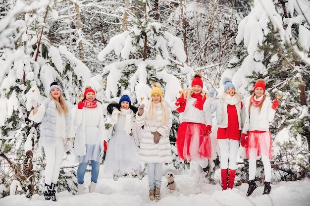 Большая группа девушек с леденцами в руках стоит в зимнем лесу. девушки в красно-белых одеждах с конфетами в заснеженном лесу.