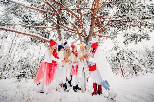 冬の森にはみかんを持った女の子たちが大勢立っています。雪に覆われた森の中で果物を着た赤と白の服を着た女の子たち。