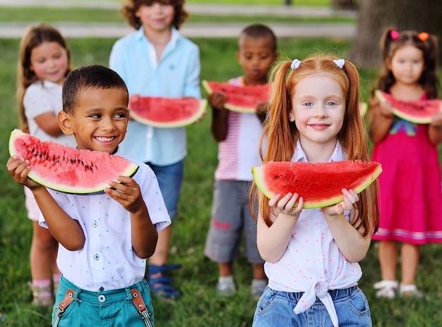 Большая группа счастливых дошкольников разных национальностей держит в руках ломтики спелого арбуза и улыбаются на фоне парка в солнечный летний день.