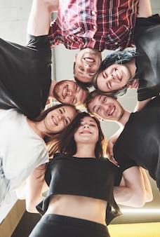 Большая группа улыбающихся друзей обнимаются вместе.