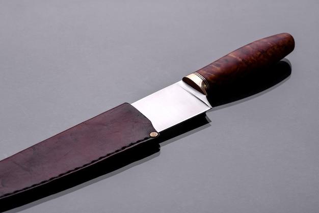 어두운 모노톤 배경에 누워있는 대형 수제 사냥 칼