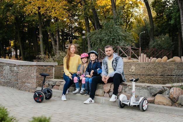 대가족이 일몰 동안 따뜻한 가을날 공원에서 세그웨이와 전기 스쿠터를 타고